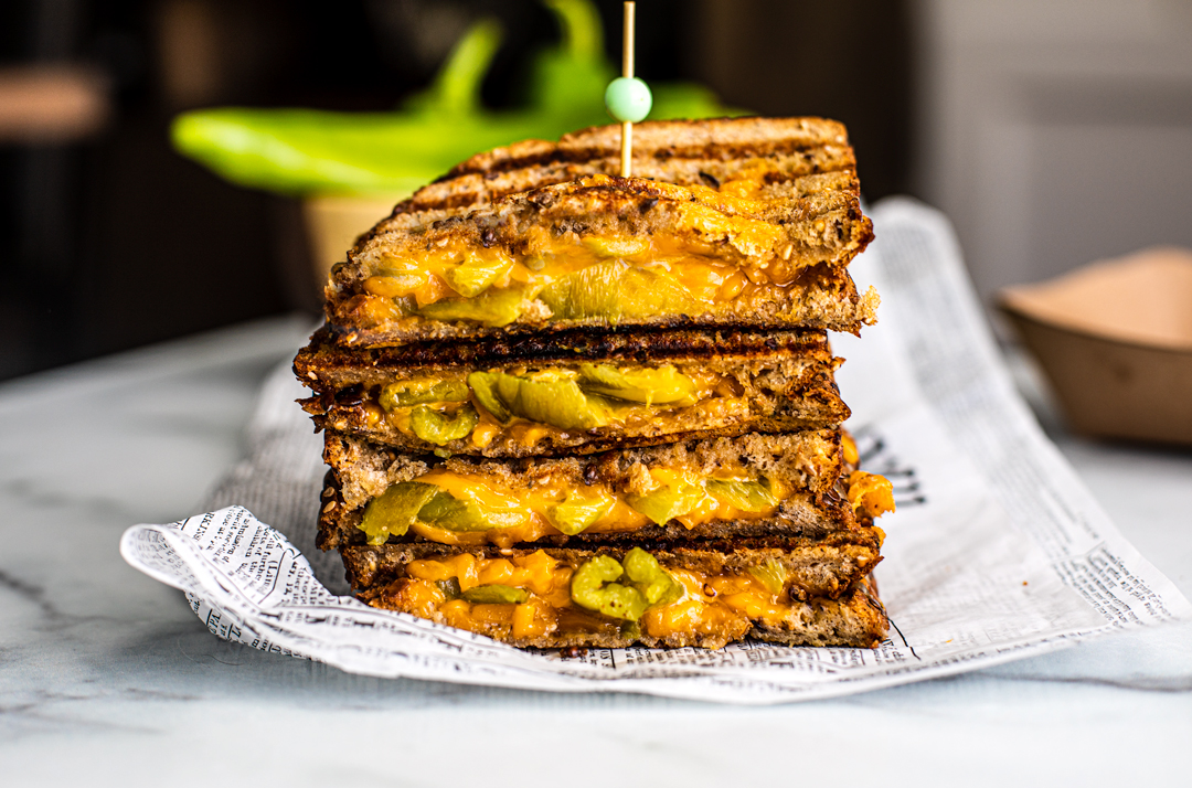 Cut halves of hatch chile grilled cheese stacked on top of one another.