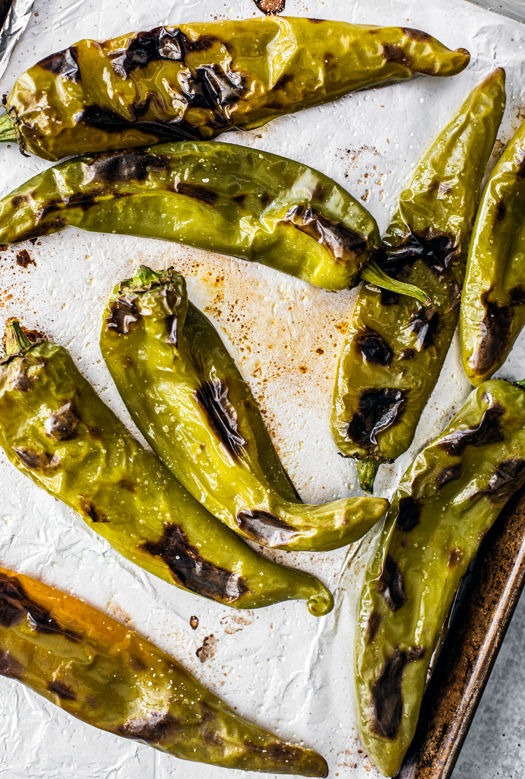 roasted hatch chiles on a baking sheet with foil.