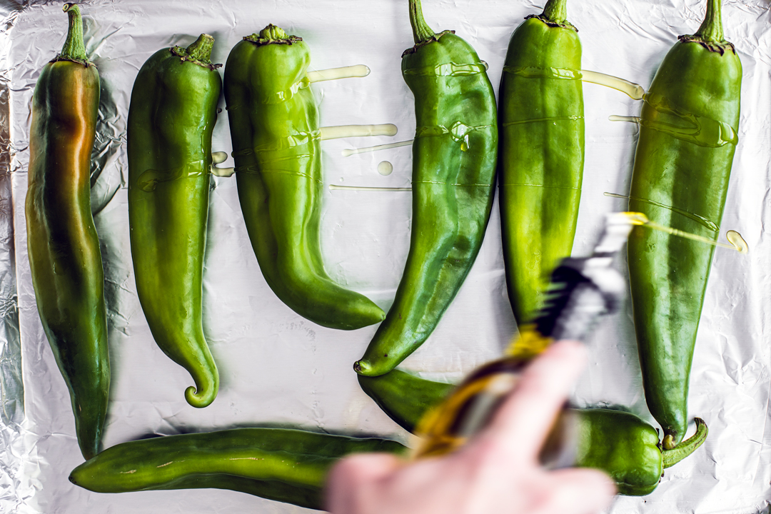 Fresh Hatch chiles on a baking sheet being drizzled with olive oil.