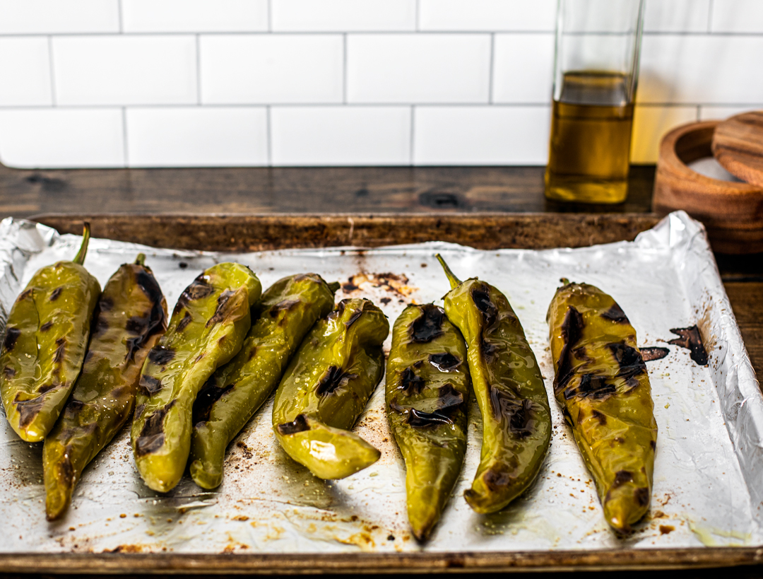 Roasted Hatch chiles on a baking sheet placed on kitchen counter.