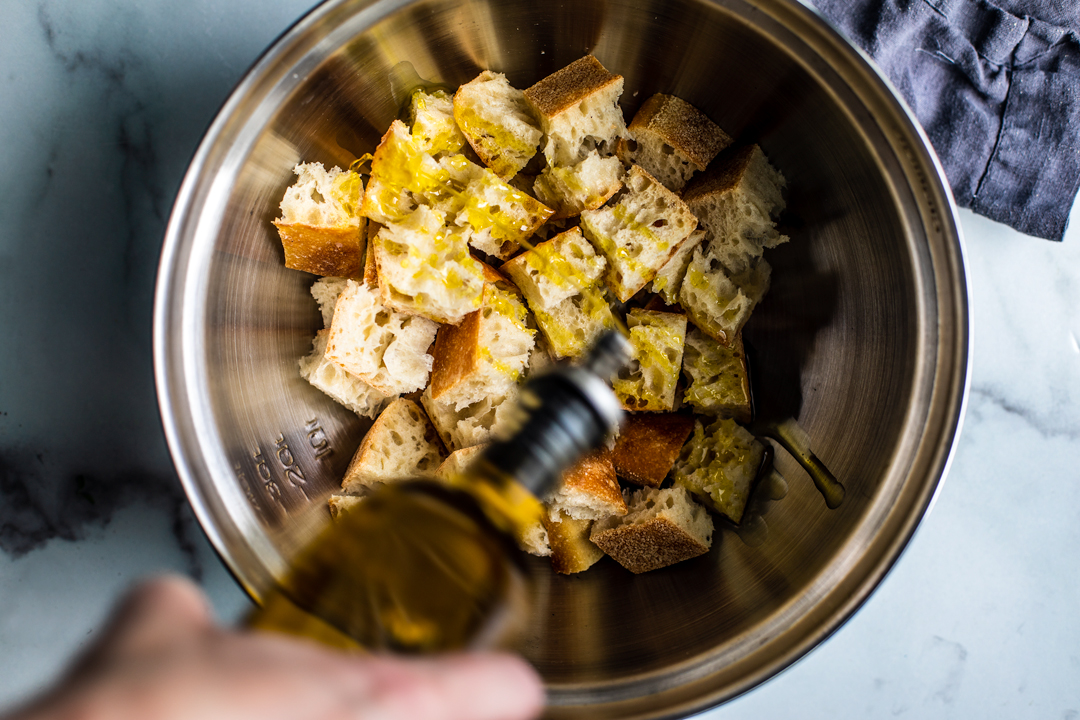 Tin bowl full of choped bread being drizzled with olive oil.