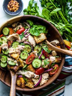 Bamboo serving bowl full of Panzanella salad and bug chunks of Genova tuna.