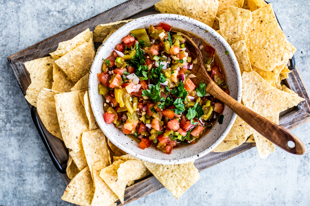 Bowl of roasted hatch chile salsa on a platter of tortilla chips.