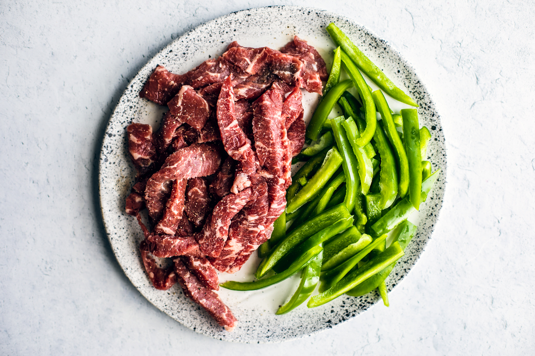 Plate of raw steak strips and green bell peppers.