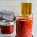 Two jars of homemade pizza sauce on a counter.