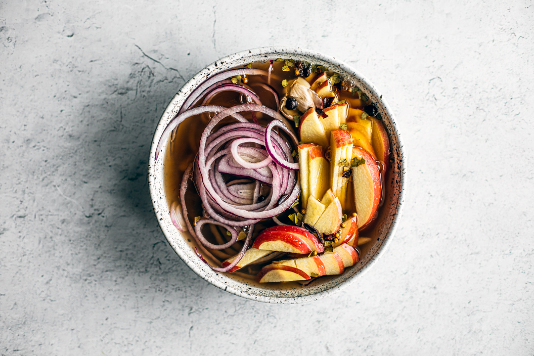 Bowl of thinly sliced red onions and apples in brine with pickling spices.