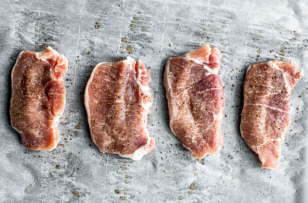 Uncooked pork cutlets on parchment seasoned with salt and pepper.