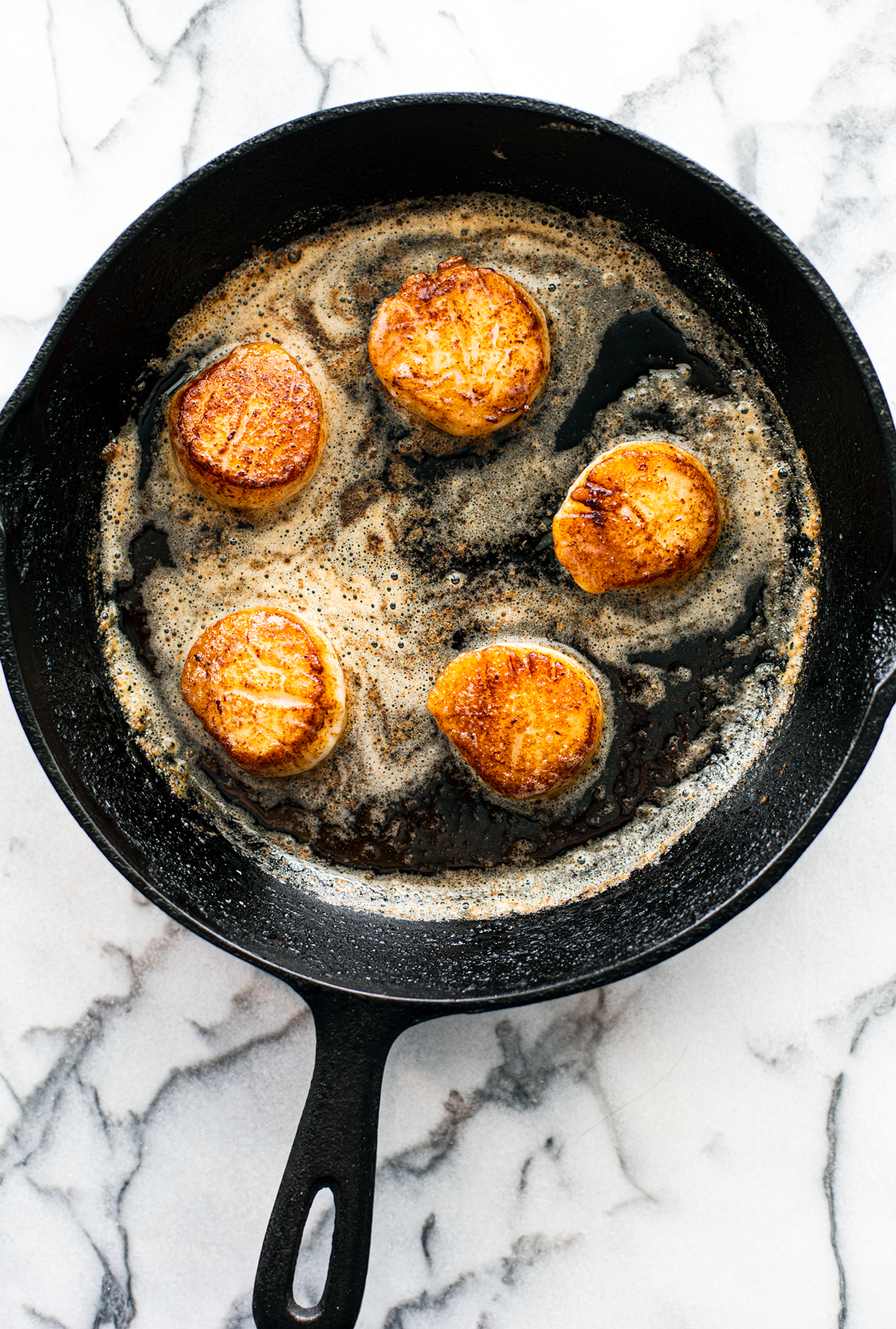 Seared Scallops in a pan with melted butter.
