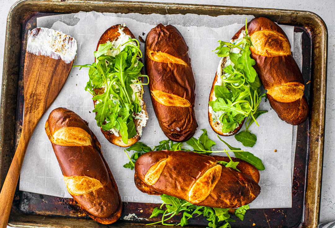 Sheet pan holding toasted pretzel buns topped with arugula with a spatula smeared with creamy horseradish sauce.