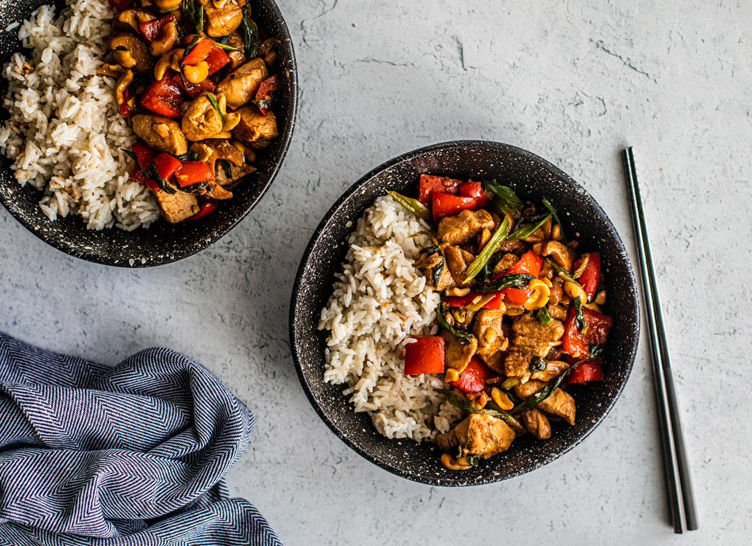 Two bowls of cashew chicken with rice and a set of chopsticks.