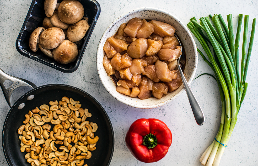 Ingredients for cashew chicken on countertop including fresh veggies, toasted cashews, and a bowl of marinated chunks of chicken.