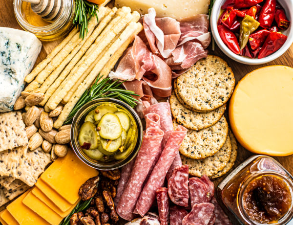 Overhead view of meat and cheese platter with nuts, fruits, jams, honey, etc.