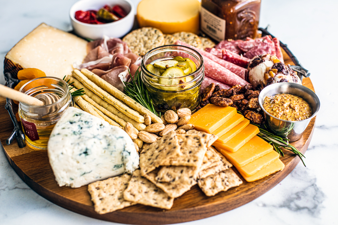 Side view of meat and cheese platter with nuts, fruits, jams, honey, etc.