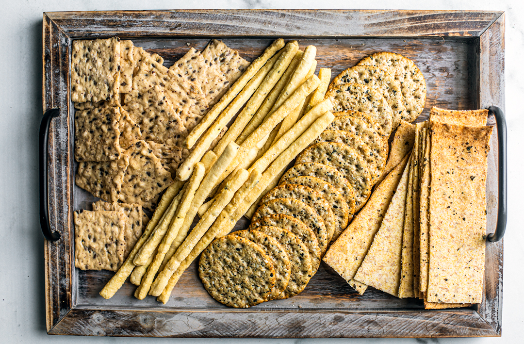 Platter full of different crackers and breadsticks.