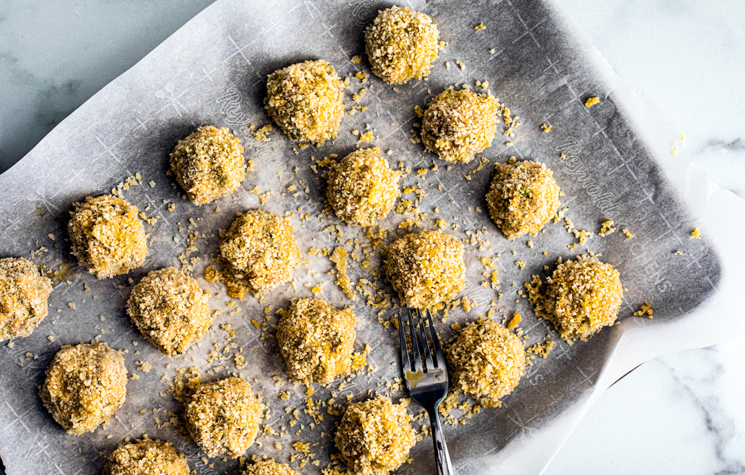 Sheet pan covered in parchment topped with uncooked croquette balls.