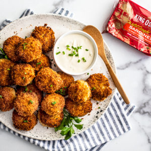 Serving platter full of crispy fish croquettes next to a tin of King Oscar sardines.