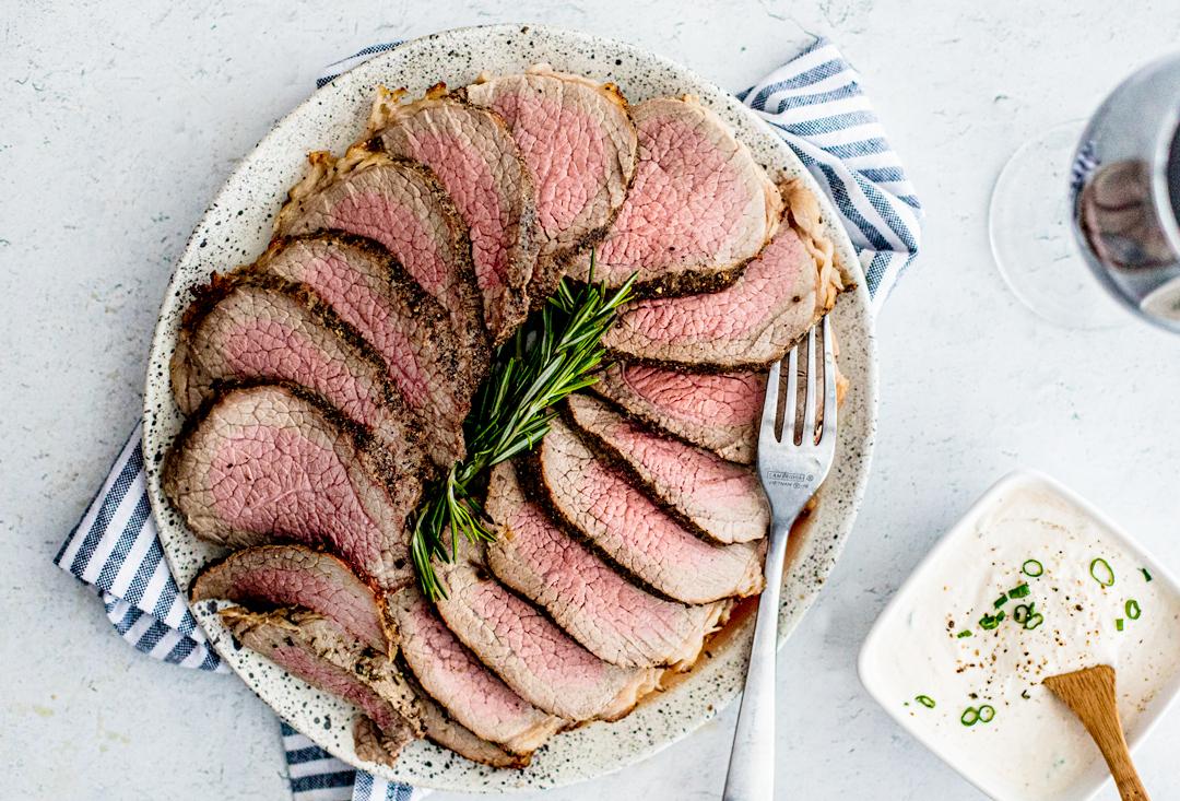 Overhead shot of platter of roast beef sliced up, medium rare.
