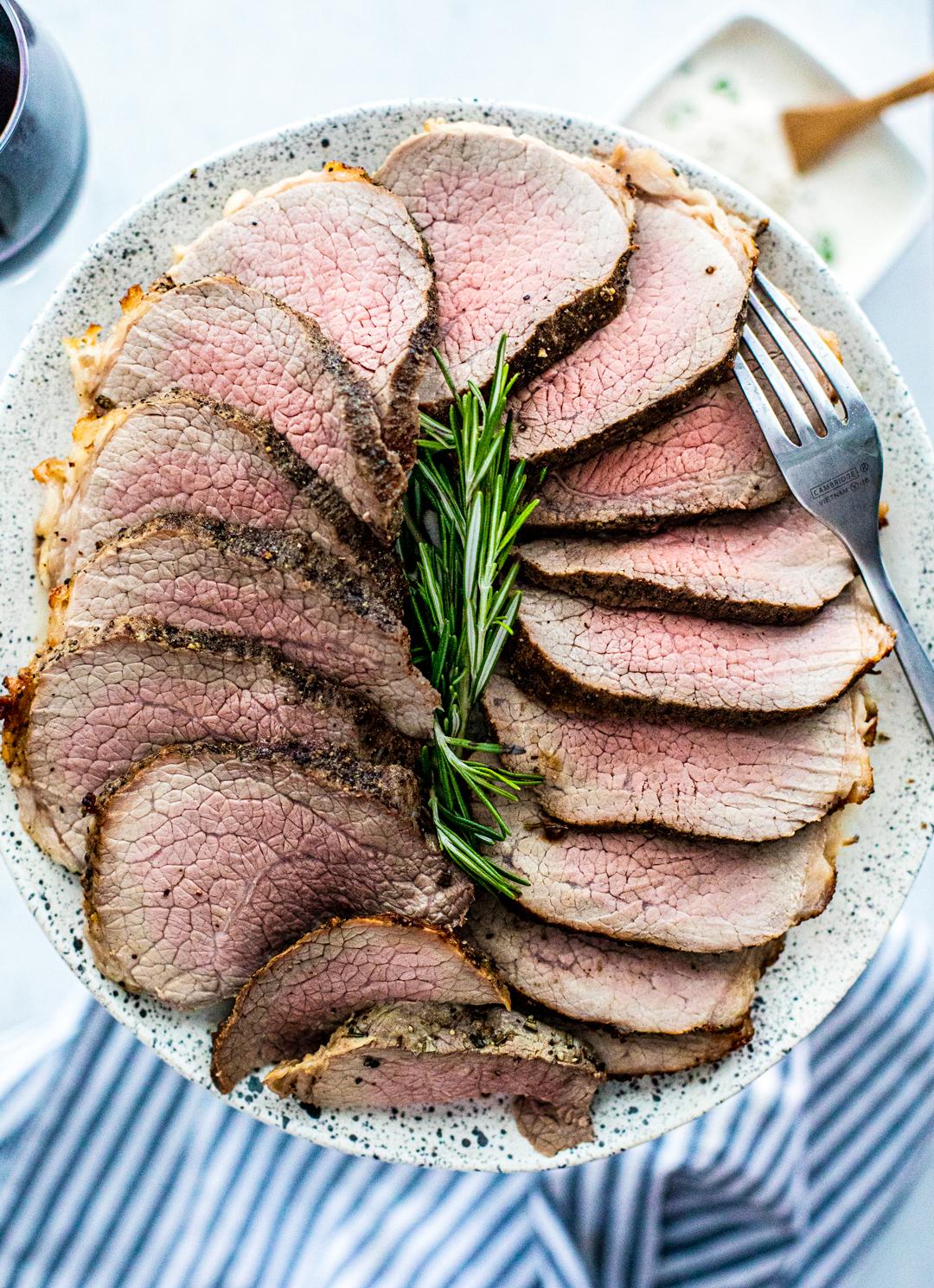 Close up of serving platter full of sliced medium rare roast.