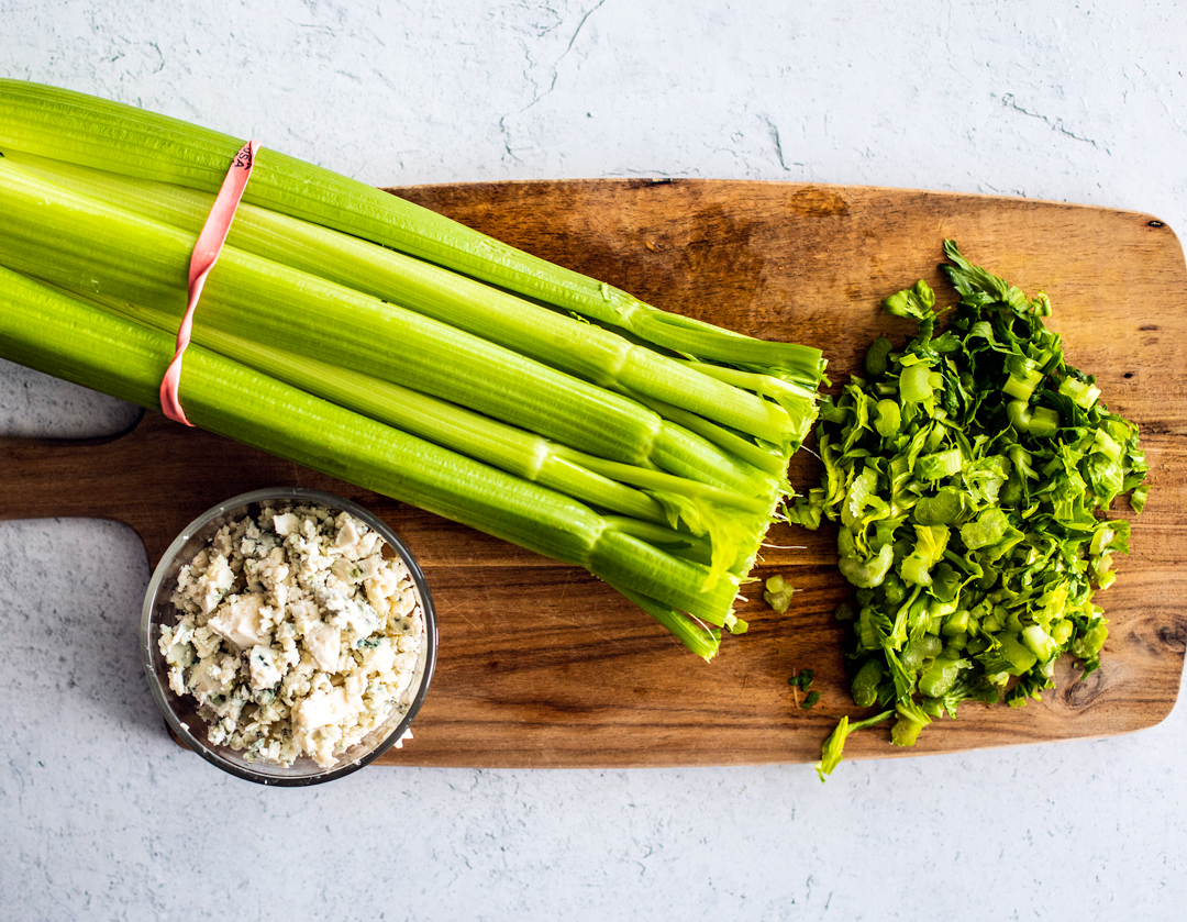 A cutting board with chopped celery on it, with a small bowl of crumbled blue cheese.