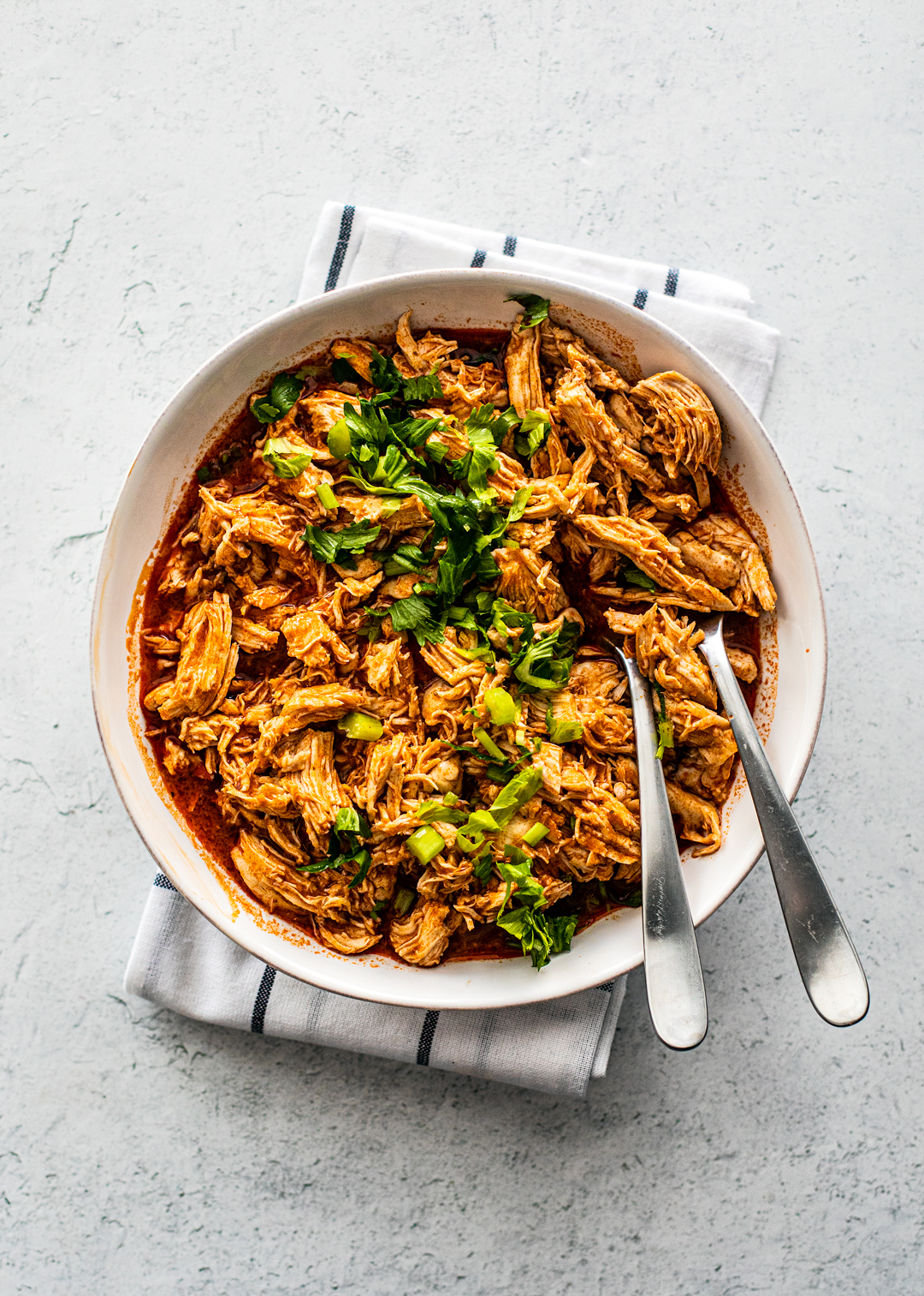 Serving bowl full of shredded buffalo chicken topped with chopped celery.
