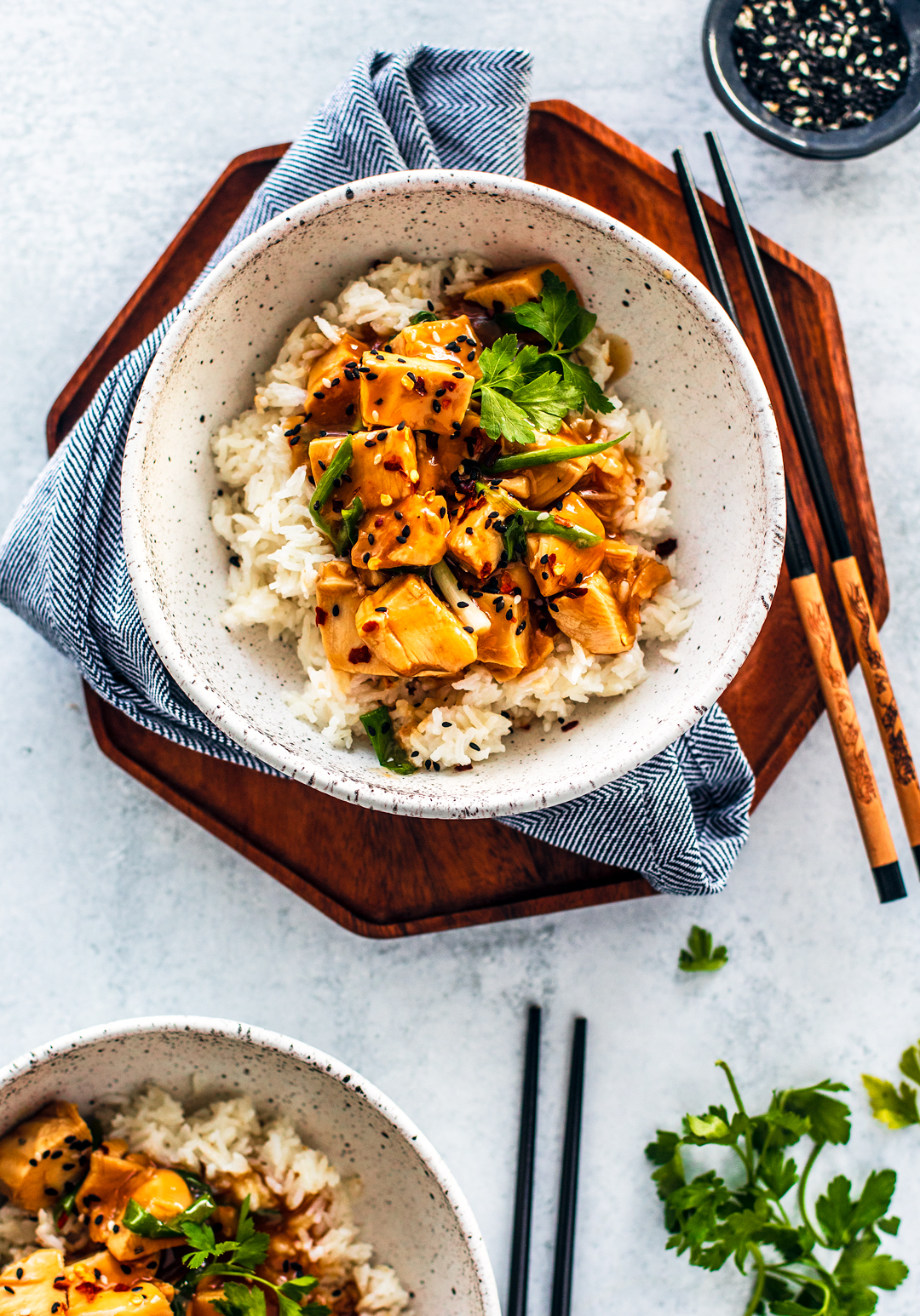 Overhead shot of bowl of rice topped with orange chicken, with chopsticks and fresh parsley beside the bowl.