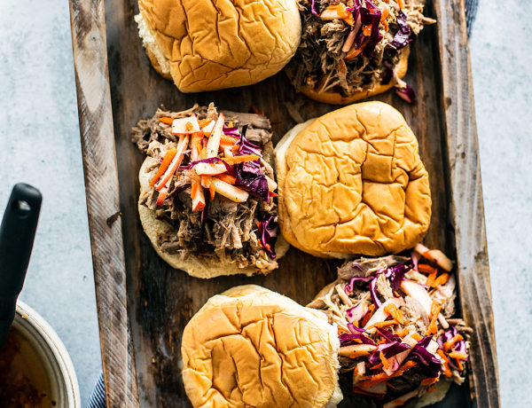 Serving tray with pulled pork sandwiches topped with apple slaw.