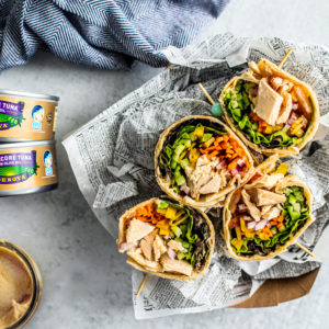 Overhead shot of wraps with jar of hummus and cans of Genova tuna.