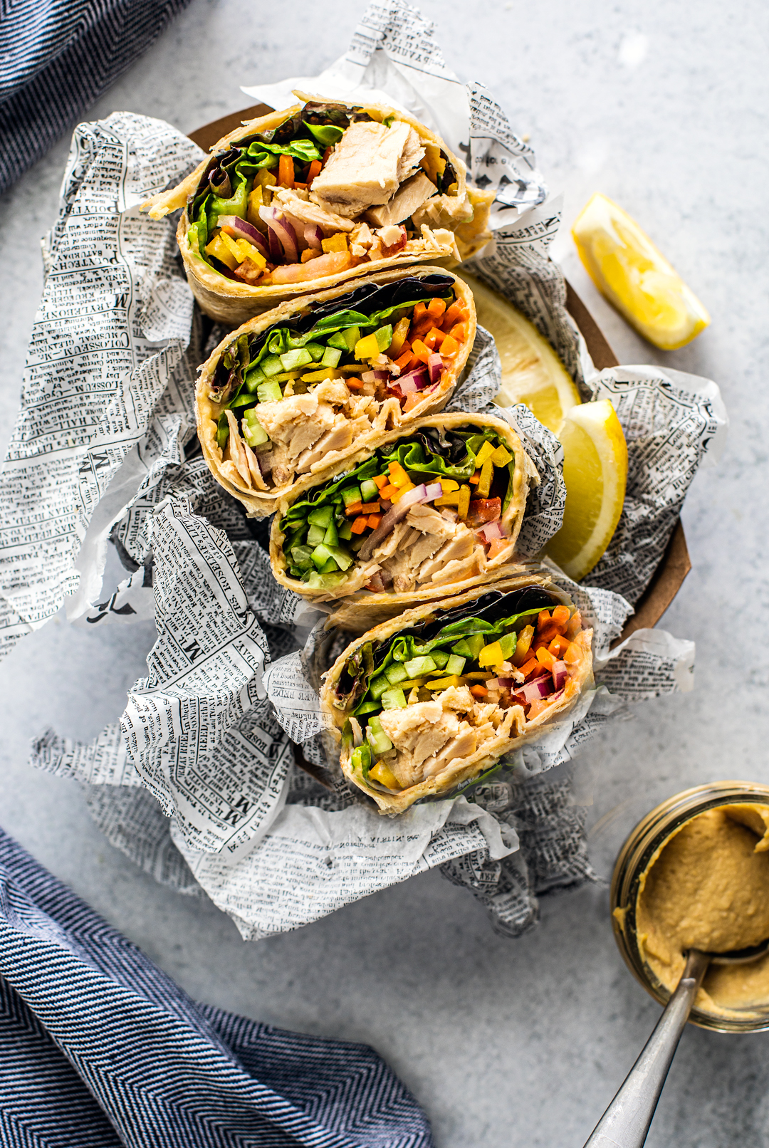 Overhead shot of colorful veggie-filled tuna wraps lined up with side of hummus.