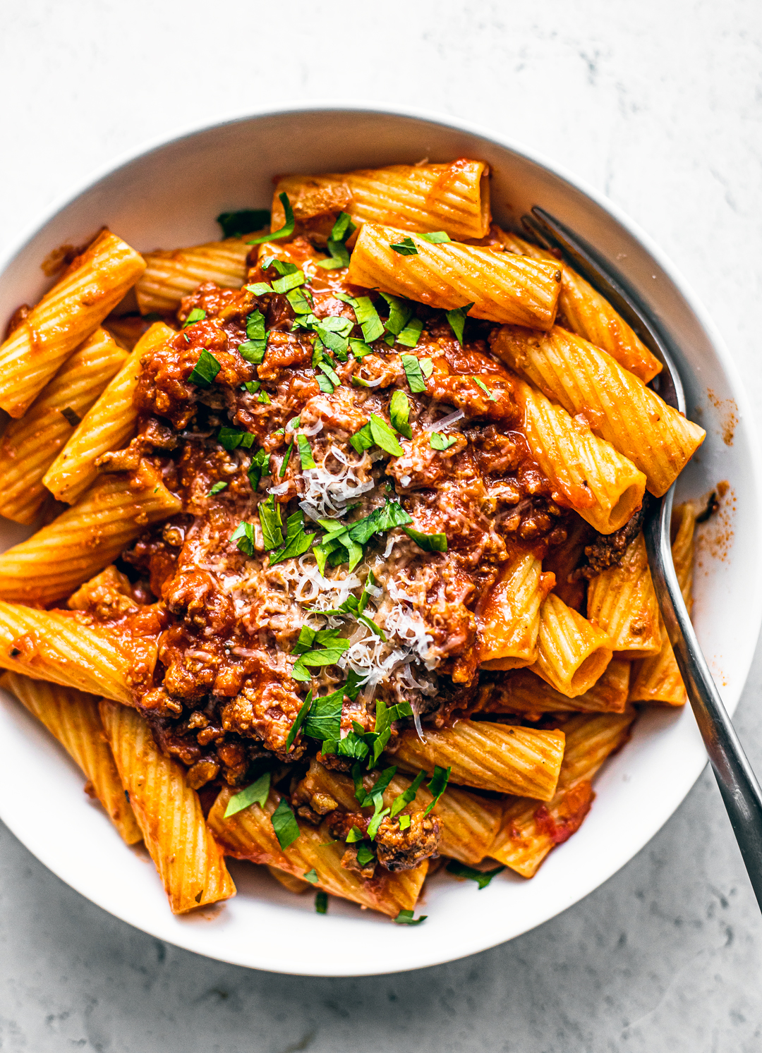 Close up of bowl of rigatoni topped with bolognese and fresh parsley.