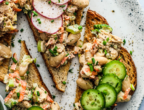 Overhead close up of fancy toasts topped with mackerel and white bean salad, radishes, and cucumbers.
