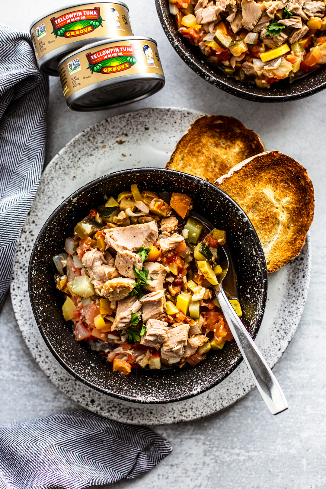 Bowl of ratatouille with tuna on a plate with crusty bread.