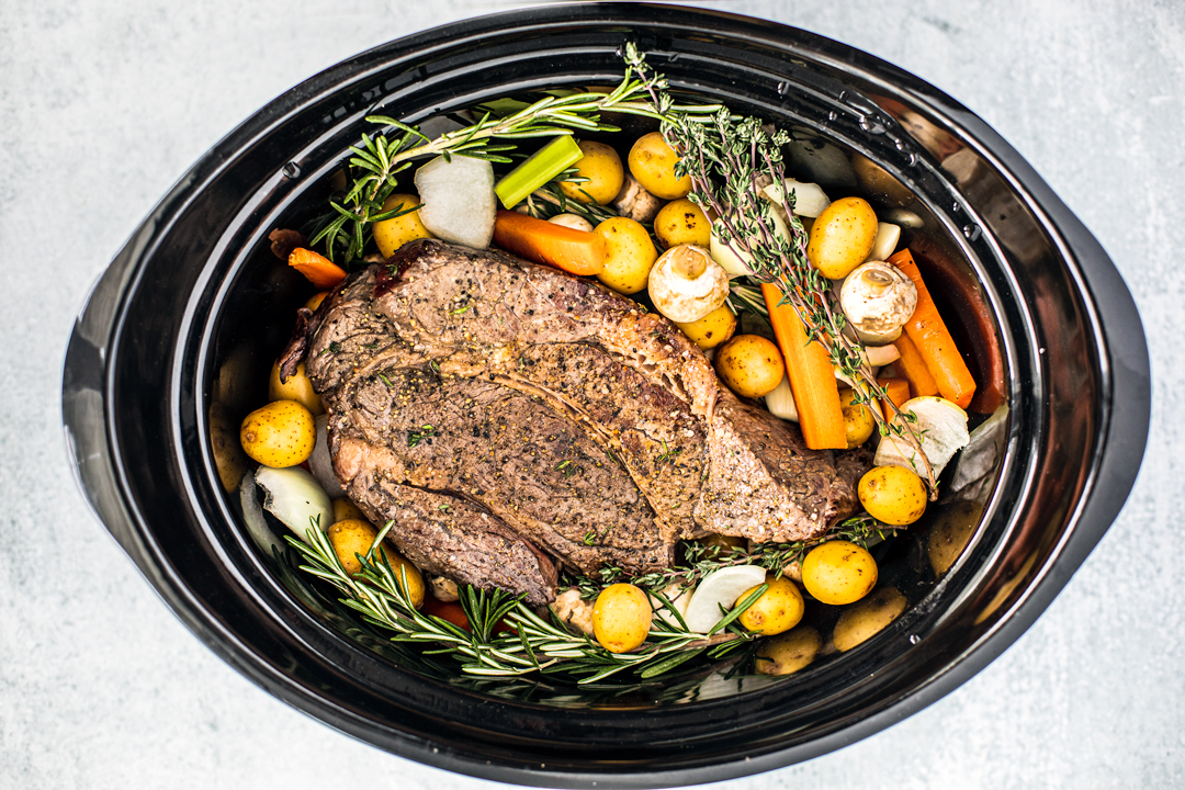 Overhead shot of uncooked pot roast, veggies, and herbs in a slow cooker.