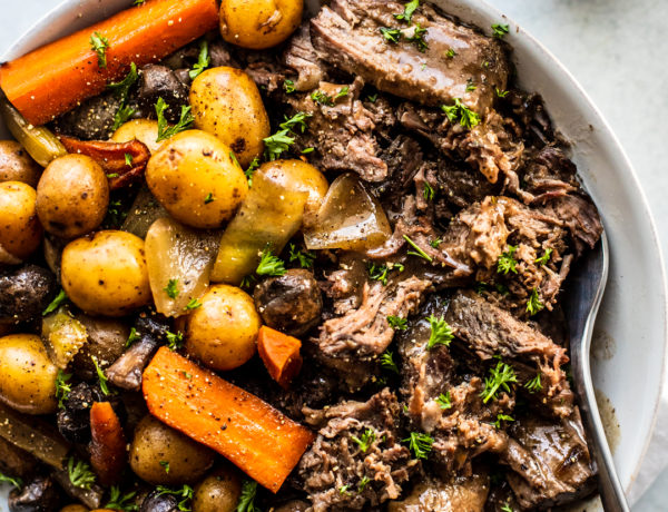 Overhead shot of shredded pot roast in serving dish with potatoes, carrots, and mushrooms.
