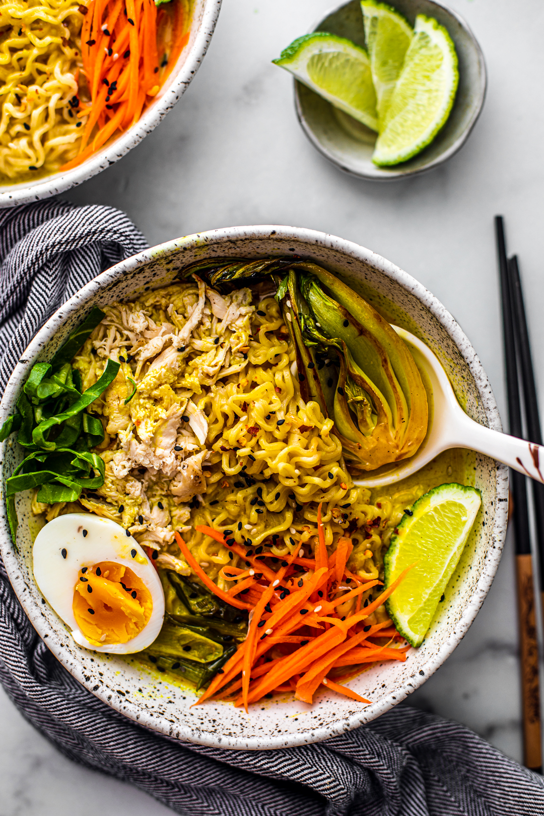 Overhead shot of bowl of chicken curry ramen soup with side of limes.