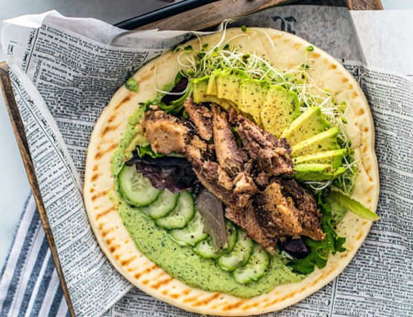 Overhead shot of pita with green goddess dressing, cucumbers, avocado, sprouts, and sardines.