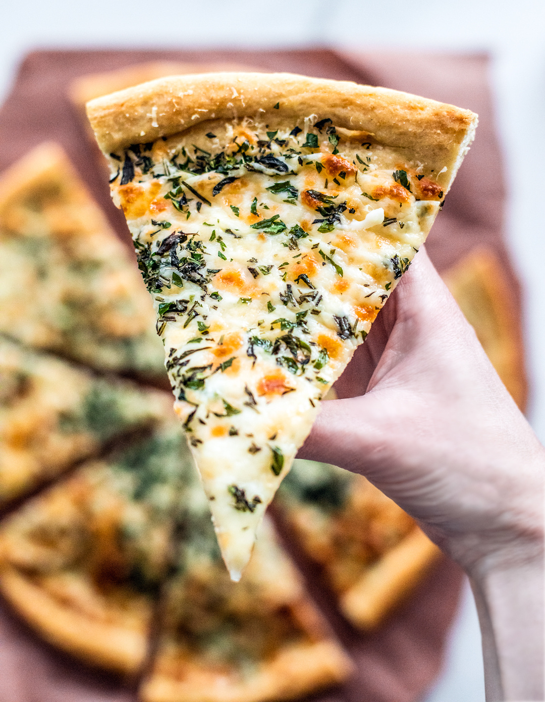 Hand holding up a slice of herb and garlic cheese pizza for a close up.