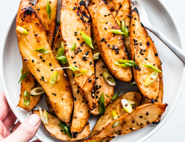 Overhead shot of hand holding up plate of honey miso roasted sweet potatoes garnished with scallions.