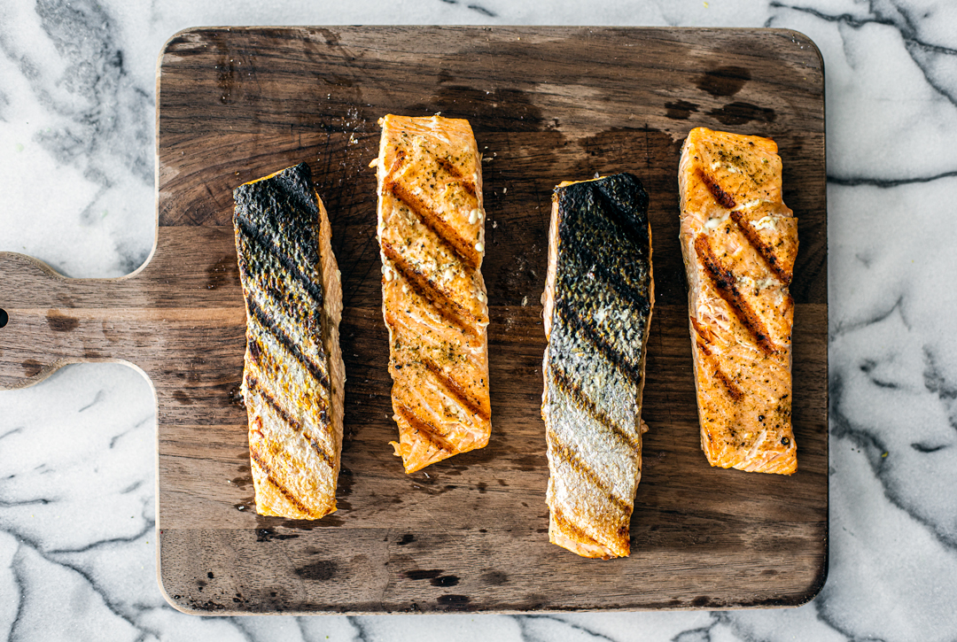 Grilled salmon fillets lined up on a cutting board.