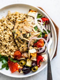 Overhead shot of plate with couscous and Greek chicken with vegetables.