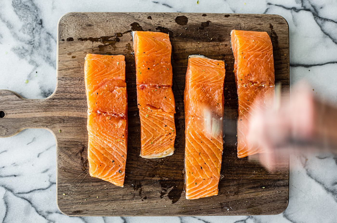 Overhead shot of fillets of salmon being brushed with oil.