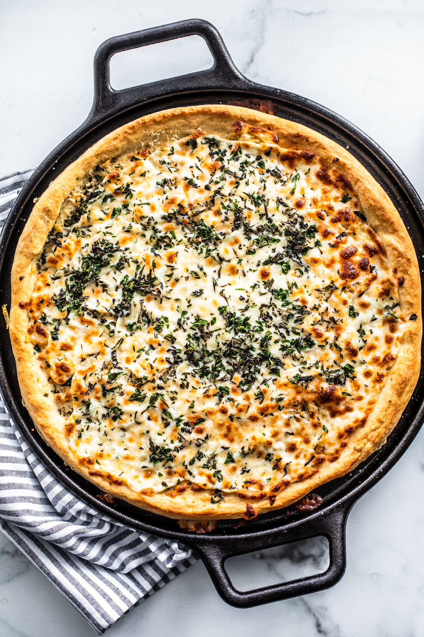 Overhead shot of cooked herb and garlic cheese pizza in cast iron pizza pan.