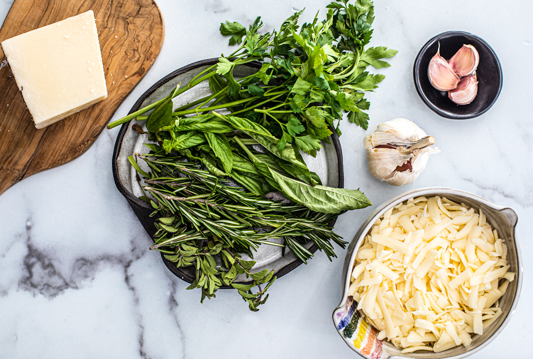 Overhead shot of ingredients: fresh herbs, parmesan cheese, shredded mozzarella in a bowl, and garlic cloves.