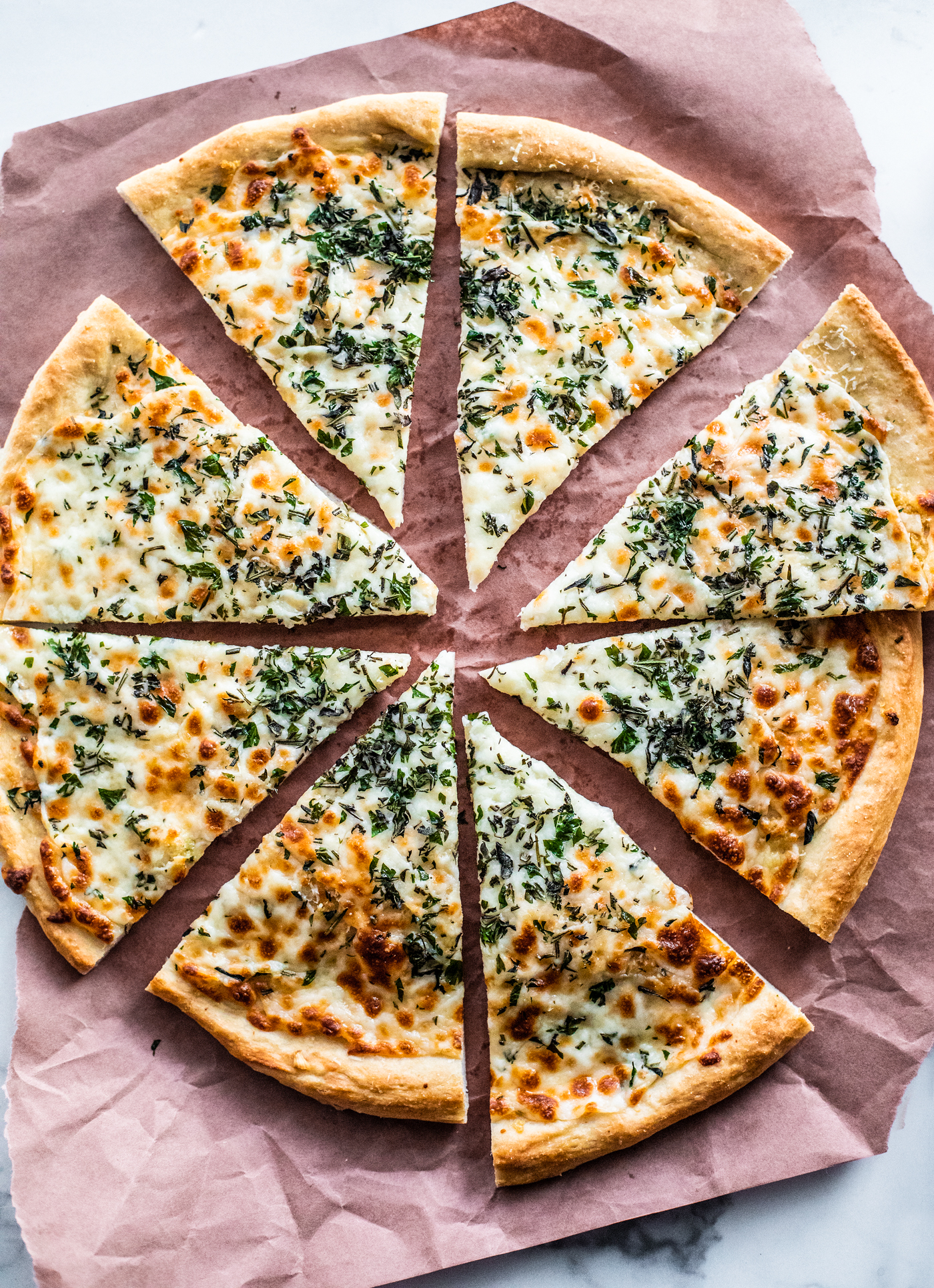 Overhead shot of cooked herb and garlic cheese pizza cut into slices on parchment paper.