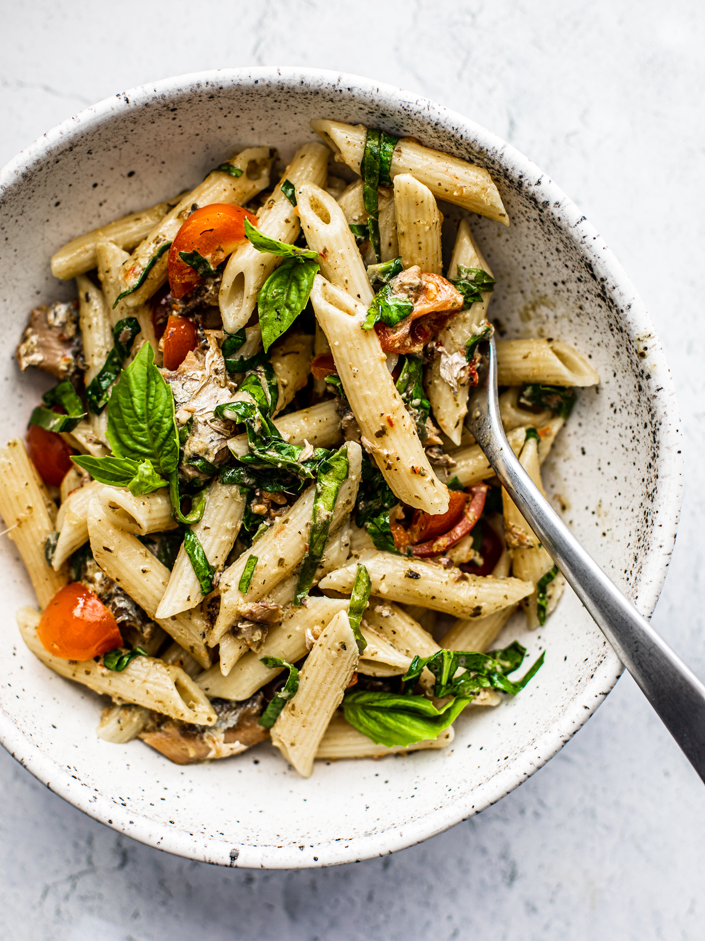 Overhead shot of a bowl of pesto pasta with tomatoes and fresh herbs.