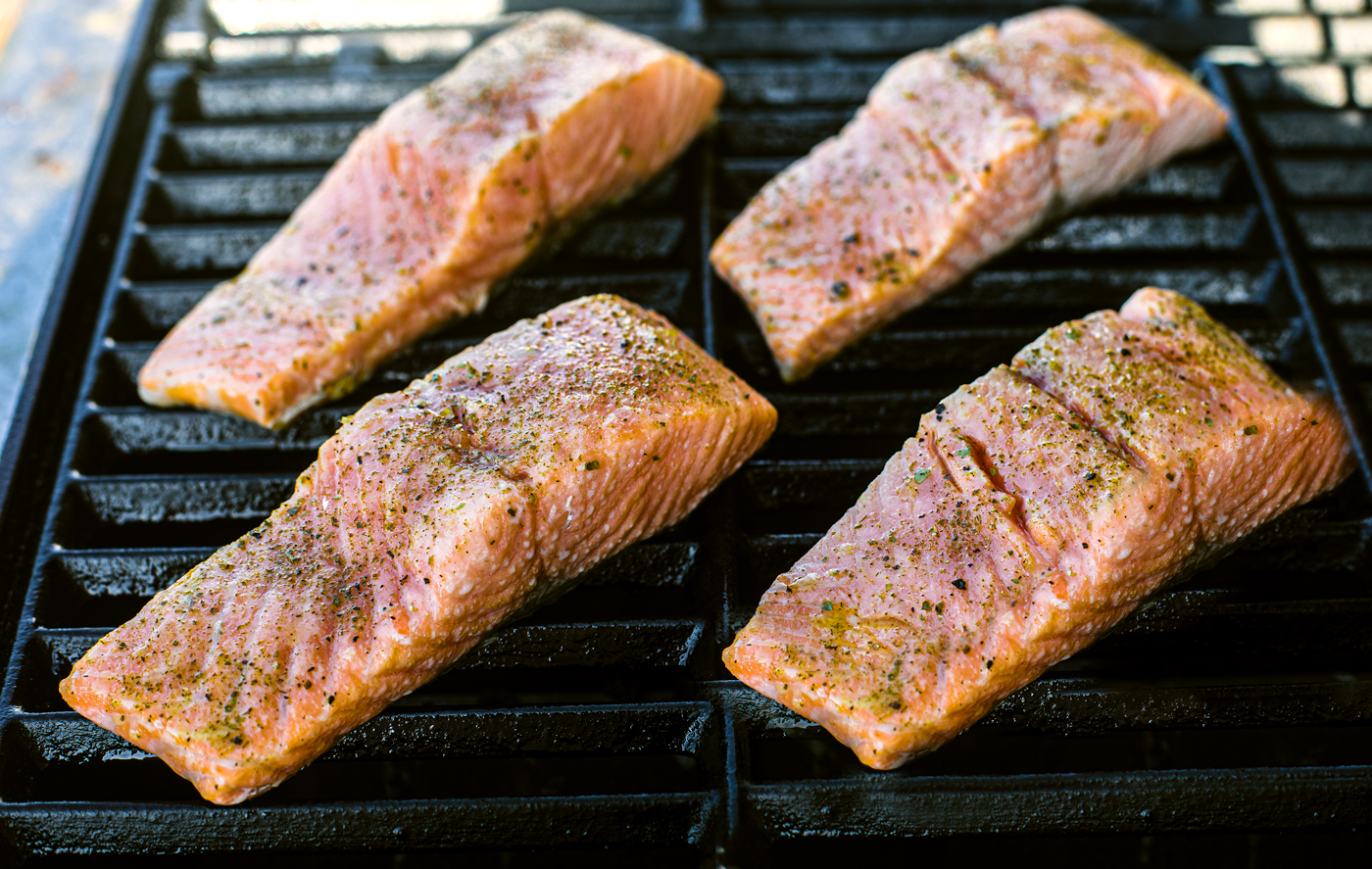 Close up of salmon fillets on grill.