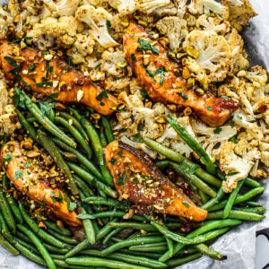 Overhead shot of sheet pan covered in green beans, cauliflower, and glazed salmon.