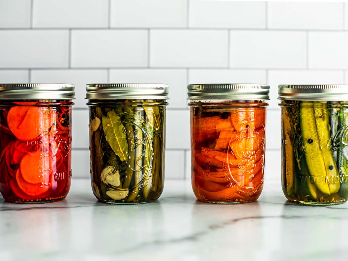 Front shot of jars of quick pickled vegetables lined up.