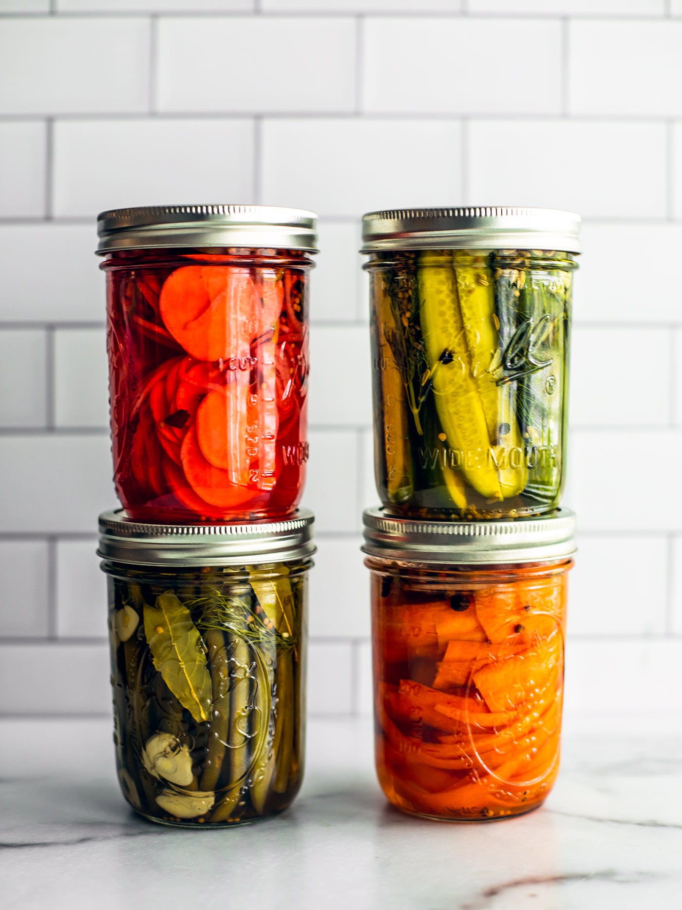 Four colorful jars of quick pickled vegetables stacked on top of on another.