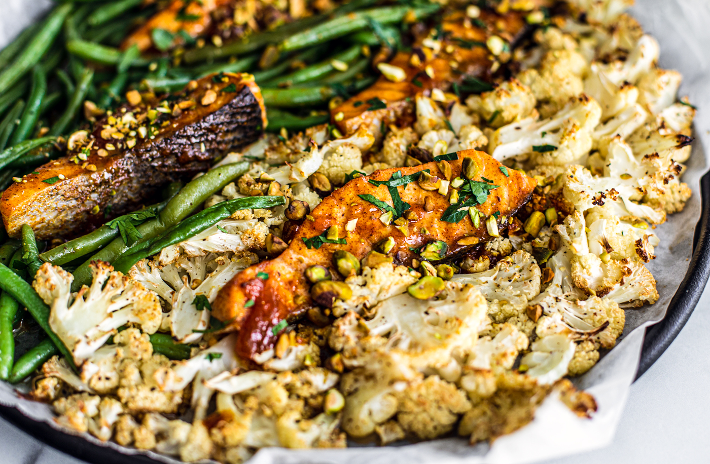 Side close up of sheet pan full of cauliflower, green beans, and glazed salmon.