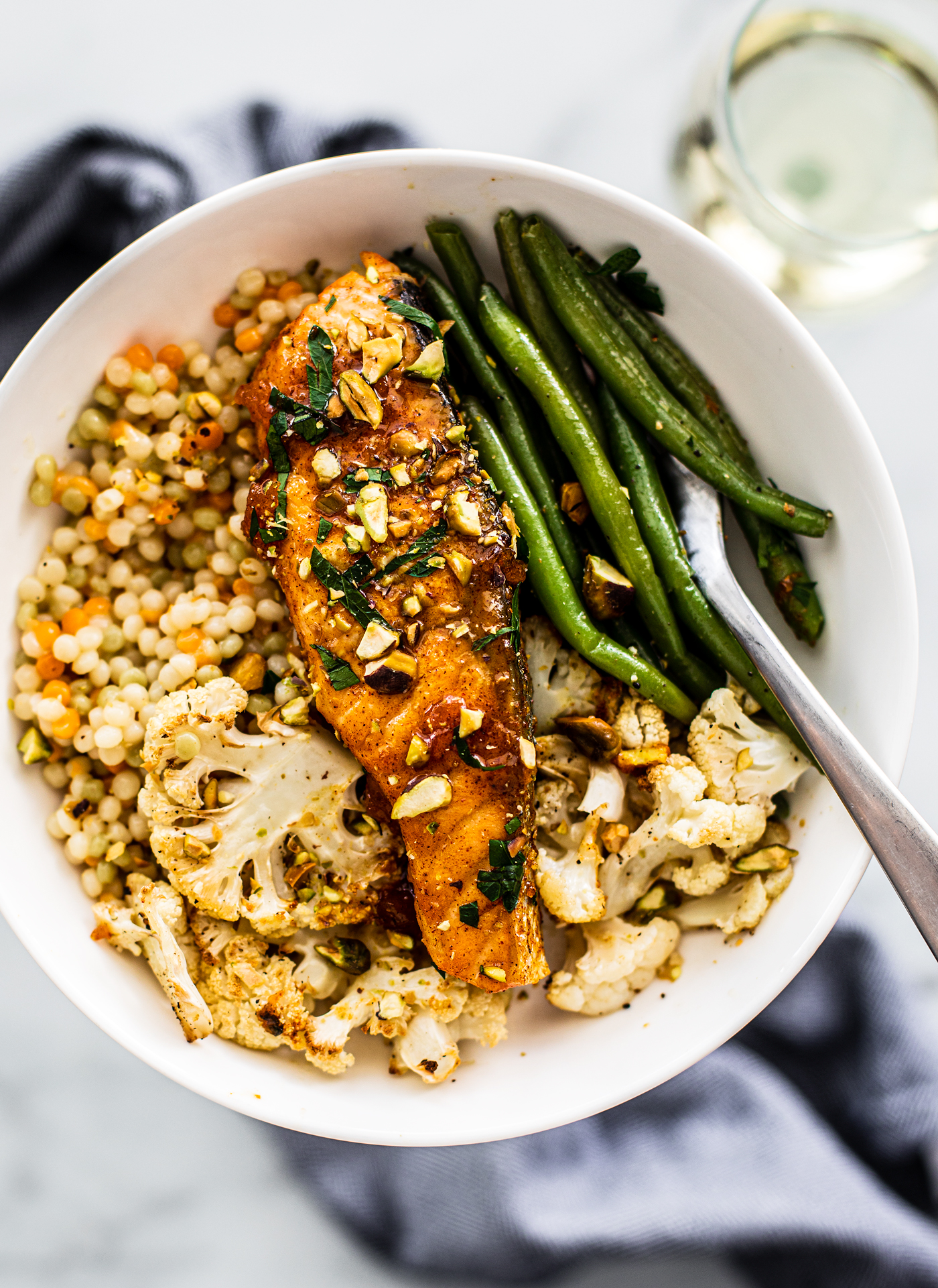 Overhead shot of serving of salmon, cauliflower, and green beans over couscous.